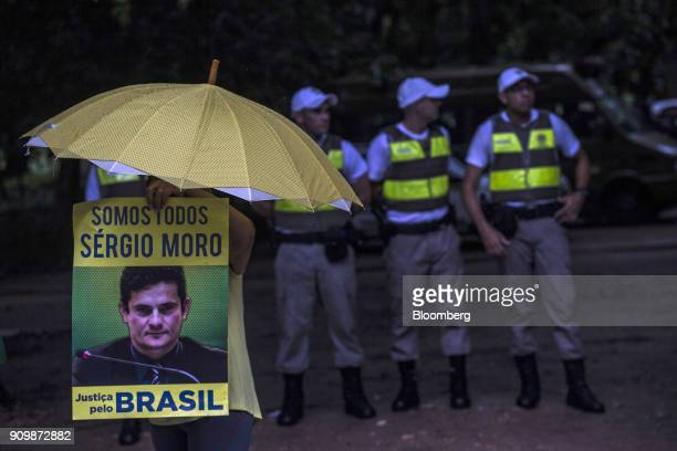 A demonstrator holds an umbrella and a sign that reads 'We Are All Sergio Moro Justice for Brazil' referring to 'Carwash' judge Sergio Moro outside...