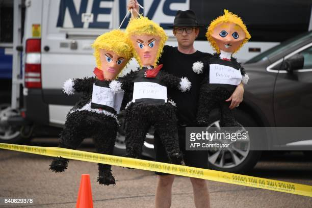 A demonstrator holds dolls of US President Donald Trump as he protests the president's visit to Corpus Christi Texas on August 29 as rains from...