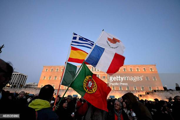 A demonstrator holds flags of ItalySpainGreeceCyprus and Portugal Greeks demonstrated all over Greece in support of the Greek government efforts to...