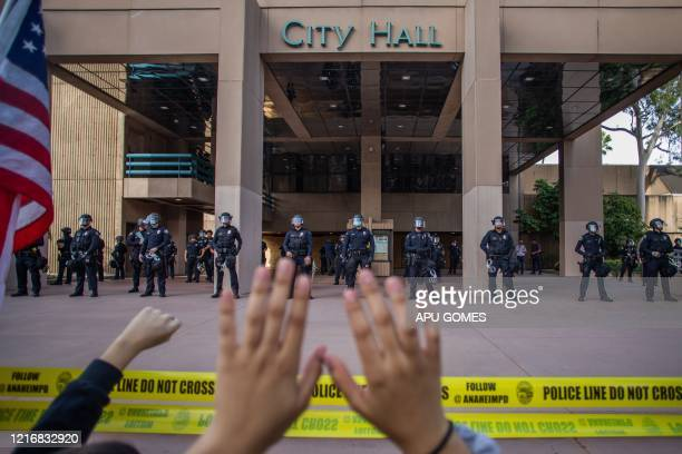 A demonstrator holds her hands up while she kneels in front of the Police at the Anaheim City Hall on June 1 2020 in Anaheim California during a...