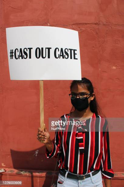 Demonstrator holds placard stating 'CAST OUT CASTE' protesting against increasing atrocities on Dalit community and Uttar Pradesh Chief Minister Yogi...