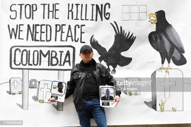 Demonstrator holds placards with the photos of social leaders killed in Colombia during the protest Demonstrators gathered outside Gibson Hall to...