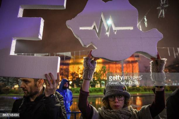 A demonstrator holds Romania's map carved with a heart beating rate graph during an antigovernmental demonstration in front of the Romanian...