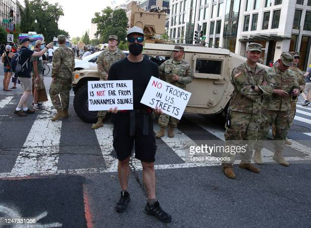A demonstrator holds signs in front of members of the National Guard while observing a peaceful protest against police brutality and racism on June 6...