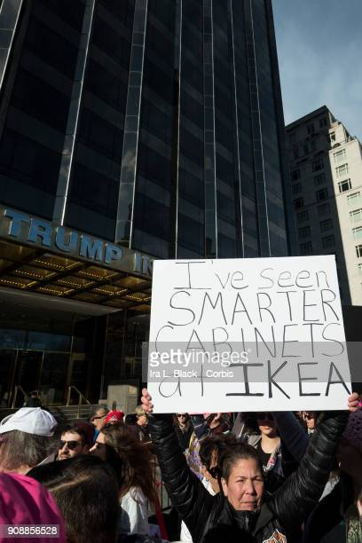 A demonstrator holds up a banner saying 'I've Seen Smarter Cabinets at IKEA' in front of Trump International Hotel and Tower during the second annual...