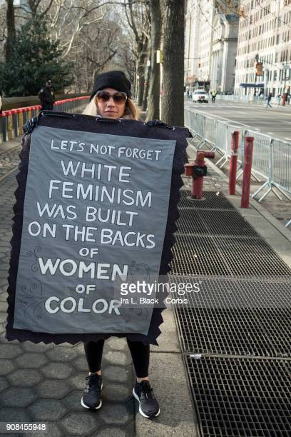 A demonstrator holds up a banner saying 'Lets Not Forget White Feminism Was Built on the Backs of Women of Color' during the second annual Women's...