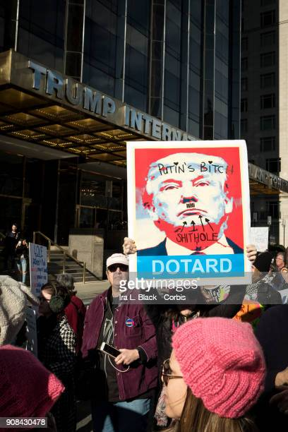 A demonstrator holds up a banner saying 'Putin's Bitch Dotard' while another has a banner saying 'We all Can Do It' in front of Trump International...