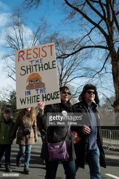 A demonstrator holds up a banner saying 'Resist the Shithole in the Whitehouse' during the second annual Women's March in the borough of Manhattan in...