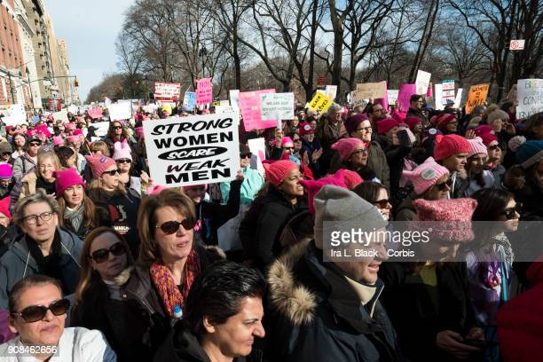 A demonstrator holds up a banner saying Strong Women Scare Weak Men among the crowd during the second annual Women's March in the borough of...