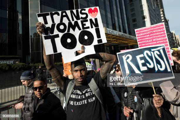 A demonstrator holds up a banner saying 'Trans Women Too' and another holds a sign that says 'RESIST' in front of Trump International Hotel and Tower...
