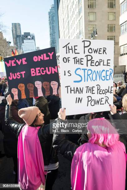 A demonstrator holds up a banner saying We've Only Just Begun while another demonstrator holds a banner saying The Power of the People is Stronger...