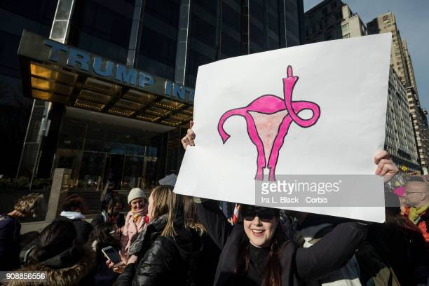 A demonstrator holds up a banner with a drawing of a female organs giving the finger in front of Trump International Hotel and Tower during the...