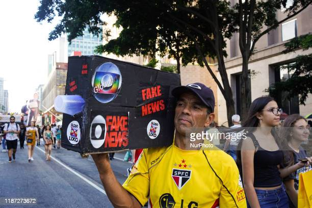 Demonstrator holds up a box that mimics a movie camera with stickers that reads quotFake Newsquot quotTrash Globequot and with the symbol of the...