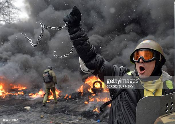 A demonstrator holds up a chain and a riot police shield as protestors clash with police in the center of Kiev on January 22 2014 At least two...