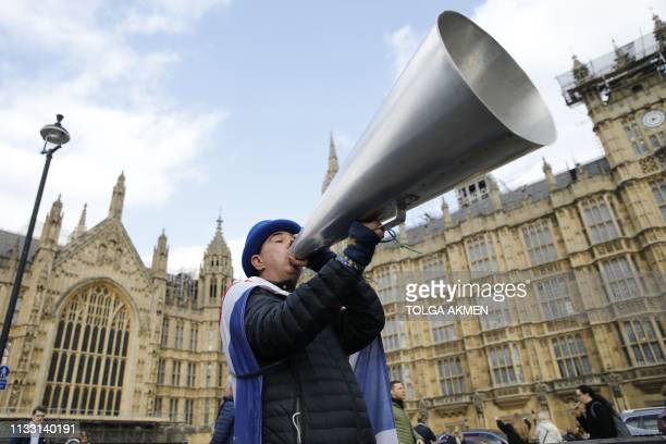 A demonstrator holds up a megaphone near the Houses of Parliament in central London on March 27 2019 Britain's divided parliament holds a flurry of...