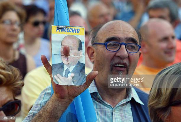 A demonstrator holds up a photograph of Italian Prime Minister Silvio Berlusconi 22 July 2003 in a central square of Rome Hundreds of leftwing...