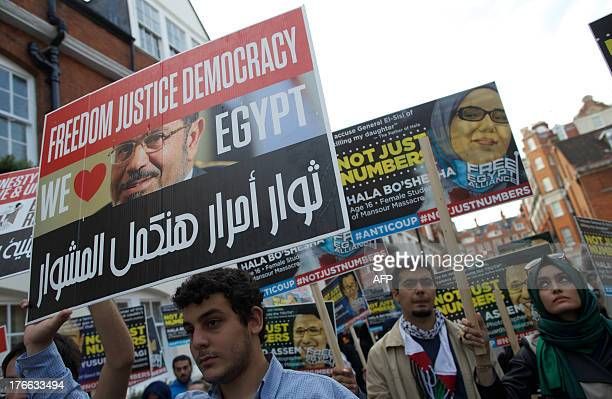 A demonstrator holds up a placard bearing the face of Egypt's ousted Islamist president Mohamed Morsi during a protest against the killing of Morsi...