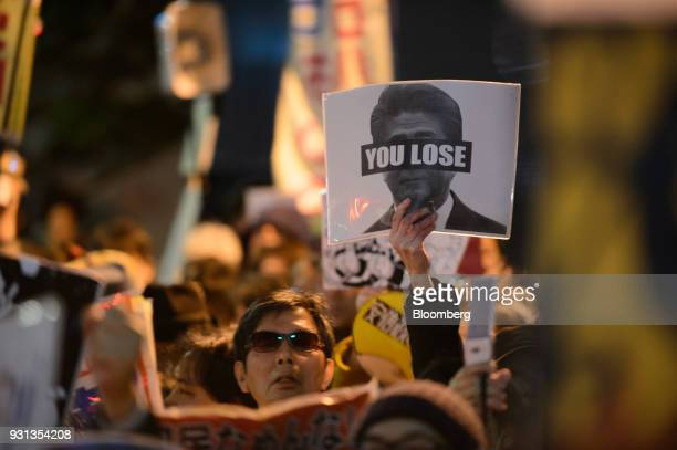 A demonstrator holds up a placard during a protest against Japans Prime Minister Shinzo Abe and Finance Minister Taro Aso in front of the prime...