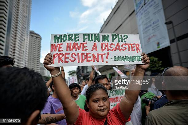 A demonstrator holds up a placard during a protest near the venue of the World Economic Forum on East Asia at the financial district of Makati south...