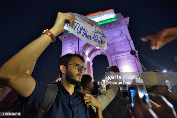 Demonstrator holds up a placard while gathered for a silent protest in solidarity with the Unnao rape case victim, at India Gate on July 29, 2019 in...