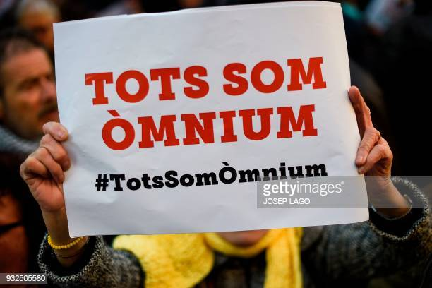 A demonstrator holds up a poster reading 'We all are Omnium' during a demonstration called by Omnium Cultural to demand a Catalan republic at Sant...