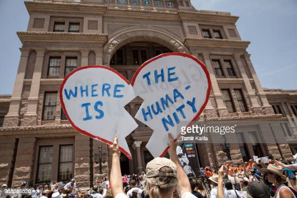 A demonstrator holds up a protest sign during a rally against the Trump administration's immigration policies outside of the Texas Capitol in Austin...