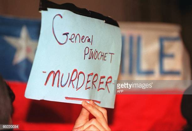 A demonstrator holds up a sign at the prestigious London Clinic 19 October where former Chilean dictator Augusto Pinochet is believed to be...