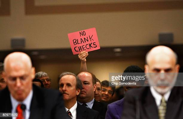 Demonstrator holds up a sign behind U.S. Treasury Secretary Henry Paulson and Federal Reserve Board Chairman Ben Bernanke during a hearing before the...