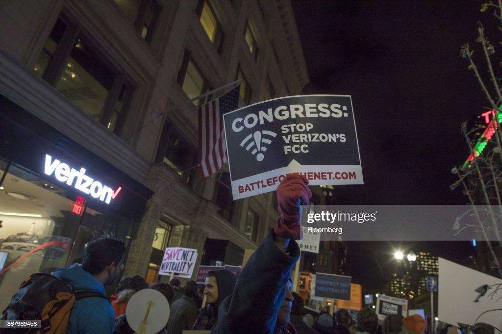 A demonstrator holds up a sign during a net neutrality protest outside a Verizon Communications Inc. store in Boston, Massachusetts, U.S., on Thursday, Dec. 7, 2017. The debate over internet regulation has steadily morphed over the last few years from an insular fight between telecom experts into a standard-issue political screaming match. Photographer: Scott Eisen/Bloomberg via Getty Images