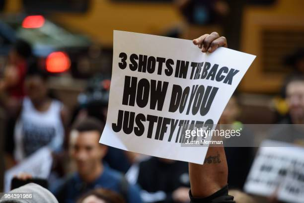A demonstrator holds up a sign during a protest a day after the funeral of Antwon Rose II on June 26 2018 in Pittsburgh Pennsylvania Rose was killed...