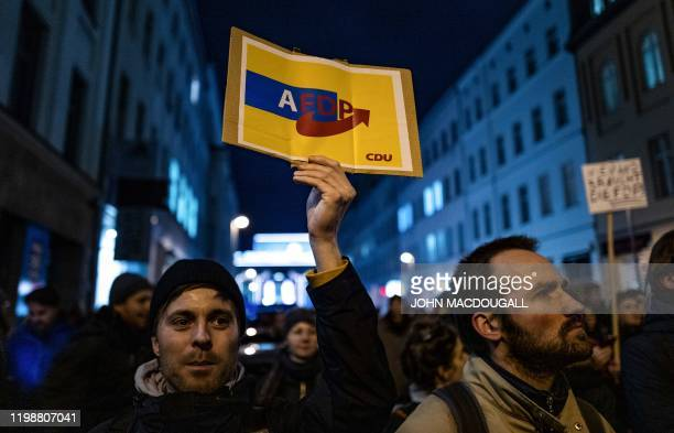A demonstrator holds up a sign featuring the three logos of the AfD FDP and CDU partiesa photo of FDP chief Christian Lindner reading Better to...