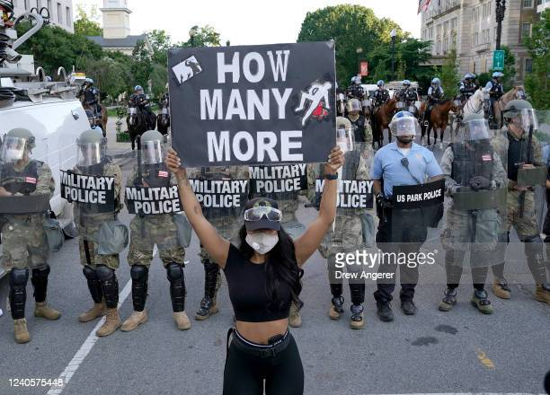 A demonstrator holds up a sign in front of a police line during a protest on June 1 2020 in downtown Washington DC Protests and riots continue in...