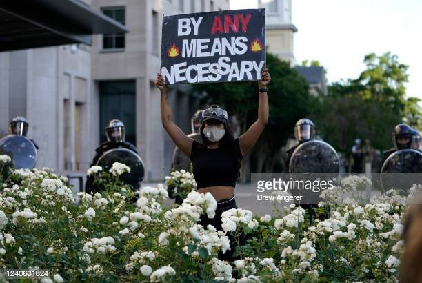 A demonstrator holds up a sign in front of a police line during protest on June 1 2020 in downtown Washington DC Protests and riots continue in...
