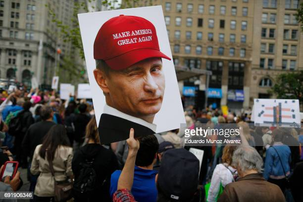 A demonstrator holds up a sign of Vladimir Putin during an antiTrump 'March for Truth' rally on June 3 2017 in New York City Rallies and marches are...
