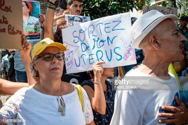 A demonstrator holds up a sign reading in French get out of my uterus during a protest outside a courthouse holding the trial of Hajar Raissouni a...