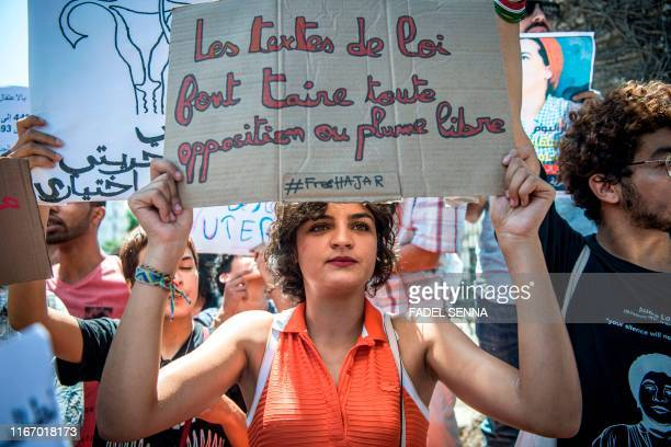 A demonstrator holds up a sign reading in French the texts of the law silence all opposition or freedom of speech during a protest outside a...