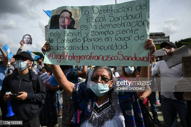 Demonstrator holds up a sign reading The dismissal of prosecutor Sandoval is the servile and complacent proof that Consuelo Porras is in favour of...