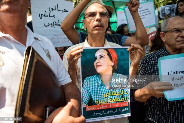 A demonstrator holds up a sign showing the portrait of Hajar Raissouni a Morrocan journalist of the daily newspaper Akhbar ElYoum with a caption...