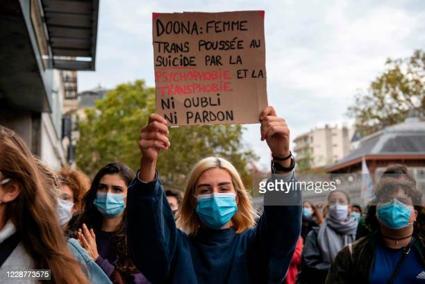 """Demonstrator holds up a sign that reads: """"Doona: trans woman driven to suicide by psychophobia and transphobia. No forgetting, no forgiveness"""", in..."""