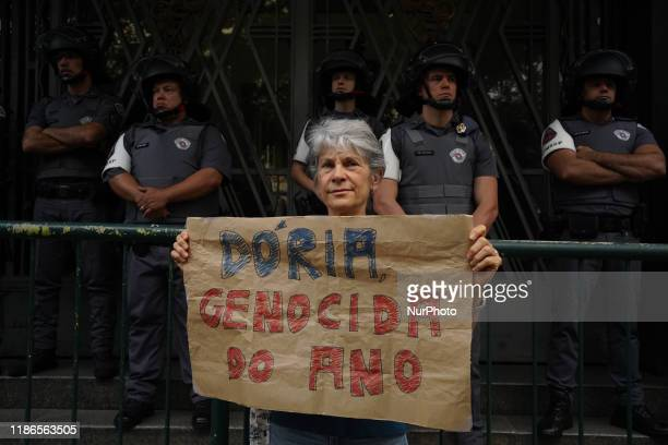 Demonstrator holds up a sign that reads Dória Genocide of the Year during a protest about the death of nine people during a police raid at a Funk...