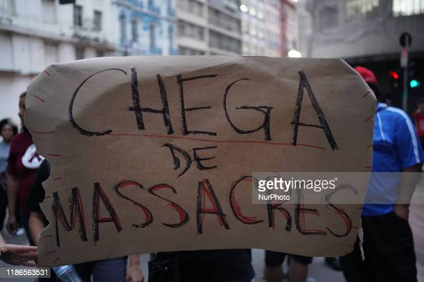 Demonstrator holds up a sign that reads No more massacres during a protest about the death of nine people during a police raid at a Funk Party at...