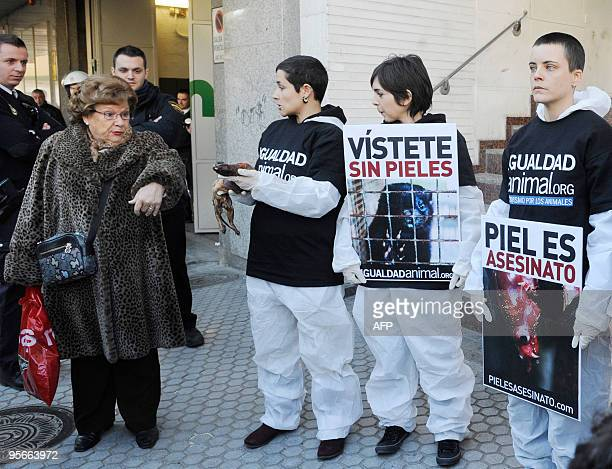 A demonstrator holds up a skinned mink in front of a shopping mall selling mink coats as other protesters hold banners to protest against the...