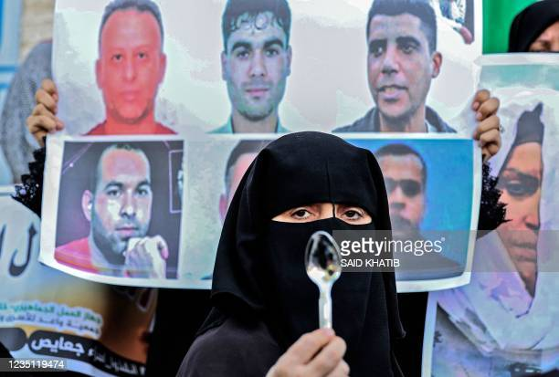 Demonstrator holds up a spoon, reportedly the digging tool used by six Palestinian prisoners who escaped from Israel's Gilboa prison, during a rally...