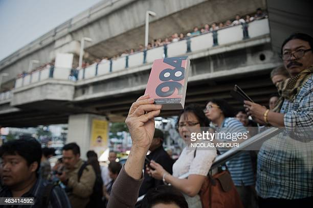 A demonstrator holds up George Orwell's book '1984' during a rally outside the Art and Cultural centre in Bangkok on February 14 2015 Dozens of...