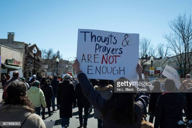 A demonstrator holds up sign 'Thoughts and Prayers are Not Enough' walking down South Street during the March For Our Lives in Morristown New Jersey...