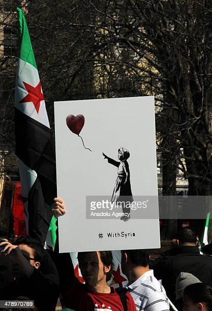 A demonstrator holds up the image of a girl holding a red heartshaped balloon by British street artist Bansky in front of the White House during a...
