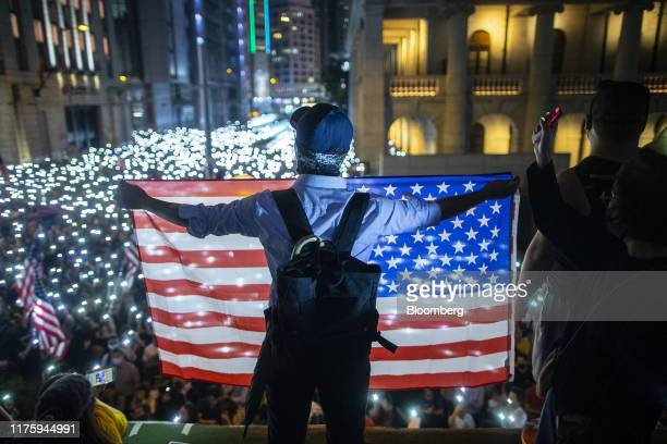 A demonstrator holds US national flag during a rally in support of the Hong Kong Human Rights and Democracy Act in Hong Kong China on Monday Oct 14...