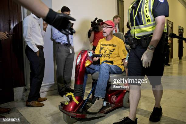A demonstrator in a scooter protesting cuts to Medicaid is led from the office of Senate Majority Leader Mitch McConnell by a US Capitol police...