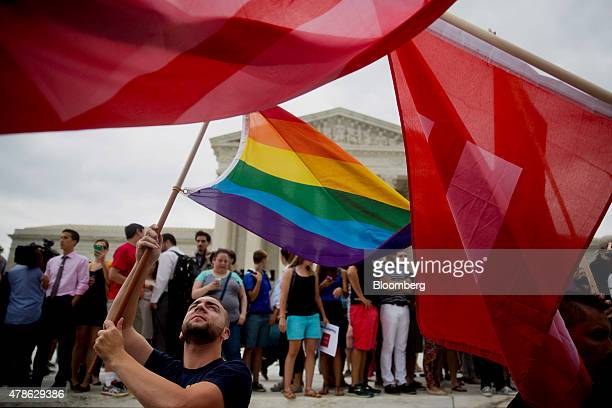 A demonstrator in support of samesex marriage waves a rainbow colored flag after the samesex marriage ruling outside the US Supreme Court in...