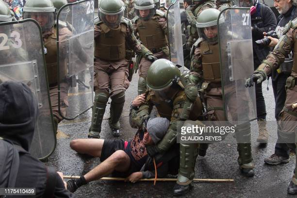 A demonstrator is arrested by Chilean riot police during a protest in downtown Santiago on October 12 during the commemoration of the Day of the Race
